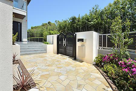 家に続く階段と、駐車場につながる石貼りのアプローチ